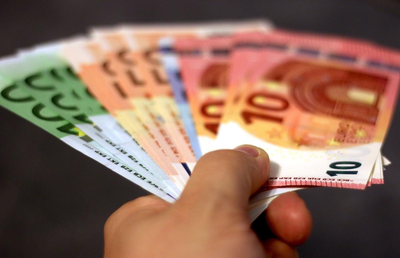 Mann streckt eine Hand mit Geldscheinen aus.