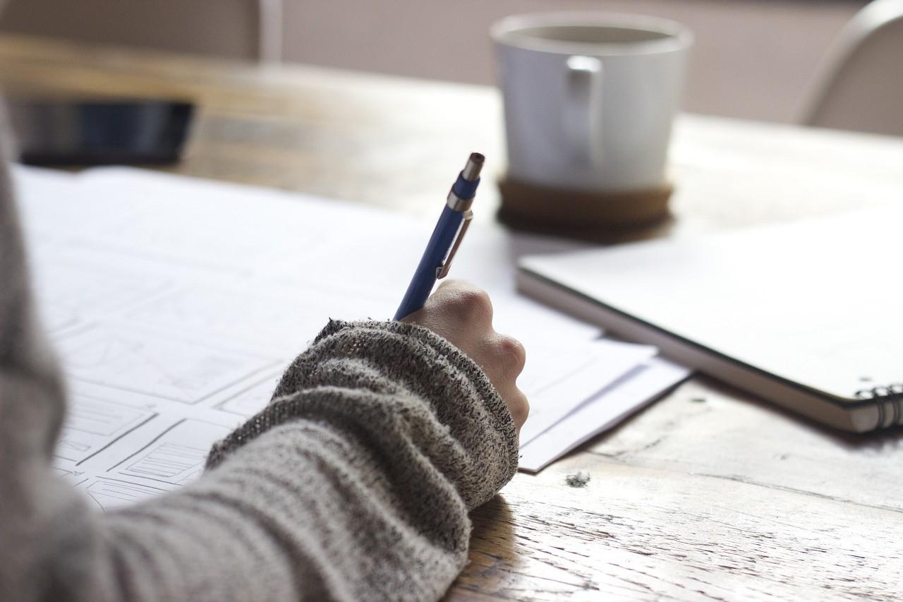 Frau notiert ihre Einnahmen und Ausgaben auf Papier.