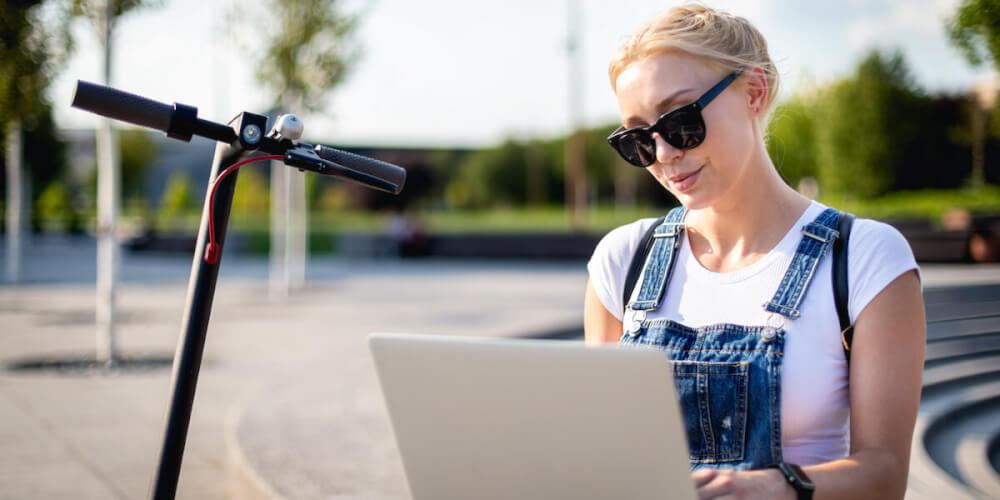 Frau beim E-Scooter-Versicherungsvergleich